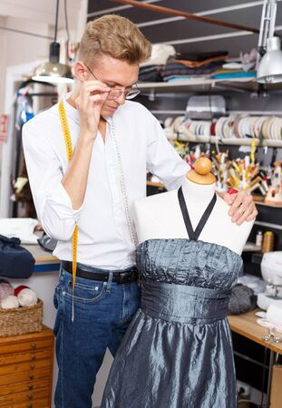 Professional tailor taking measurements of dummy for tailoring dress