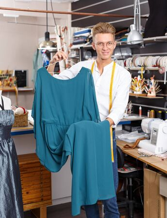 Portrait of blond male tailor holding dress at his workplace in sewing atelier