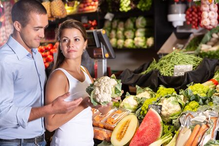 Portrait of happy man and woman choosing vegetables in shop Stockfoto