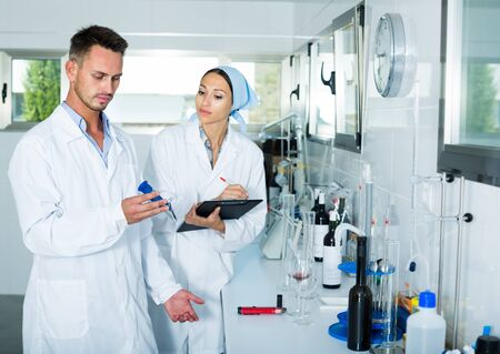 young man and woman experts in withe coats analyzing wine quality in wine manufactory laboratory. Focus on man Stockfoto
