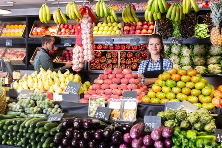 Posing fine woman and working man in fruit and vegetable shop Stockfoto