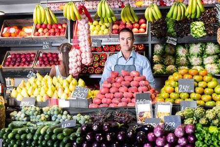 Friendly happy  positive smiling man and woman laying out vegetables and fruits in shop