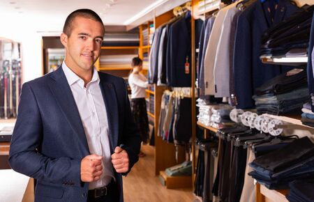 Portrait of male client choosing classic jacket in the mall