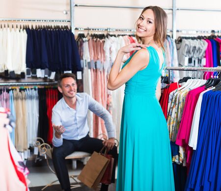 Cheerful female is trying on new blue dress in boutique.