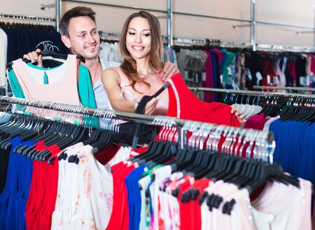 Young spanish woman and man looking for new dress in showroom