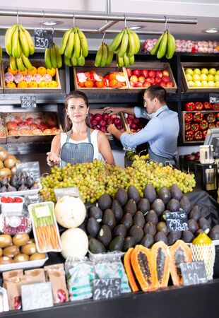 Portrait of welcoming positive cheerful smiling female shop assistant and working male seller in fruit shop Stockfoto