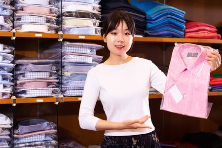 Adult Chinese salesgirl offering stylish pink dress shirt in men clothing store