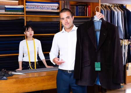 Satisfied male client of sewing workshop showing his new suit jacket on background of young Chinese female tailor