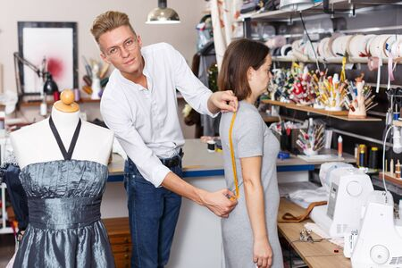 Young male tailor using tape measure for taking measurements of female customer at sewing atelier