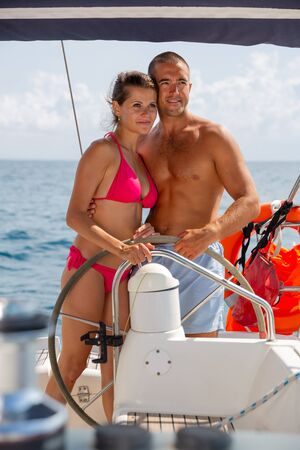 Young man and woman steering pleasure yacht, enjoying romantic sea travel on warm summer day
