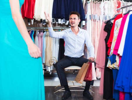 cheerful russian  man smiling and offering dresses in women clothing store Stockfoto