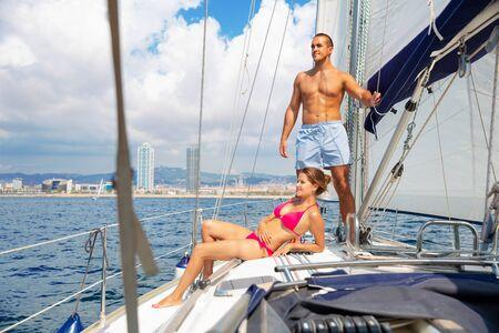 Young loving glad pleasant beautiful  couple enjoying sea trip on pleasure sailboat along coast of Barcelona on sunny summer day Stok Fotoğraf - 129856985
