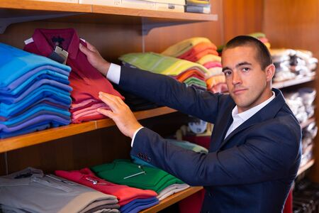 Male seller lays out shirts on shelves in clothing store