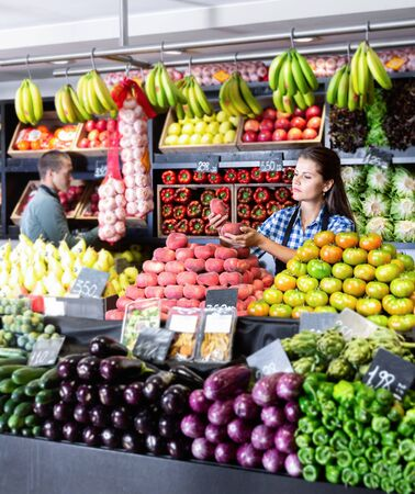 Friendly glad  positive man and woman laying out vegetables and fruits in shop