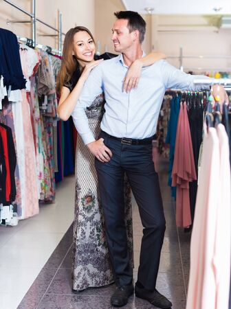 pair of young people in women clothes boutique choose dresses Stockfoto