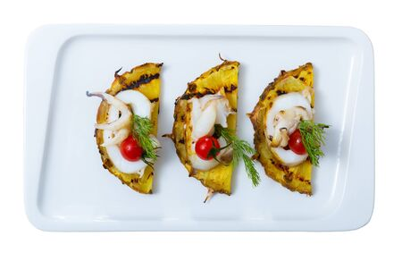 Cuttlefish grilled with pineapple and cherry tomatoes and sweet and sour sauce Chile. Isolated over white background