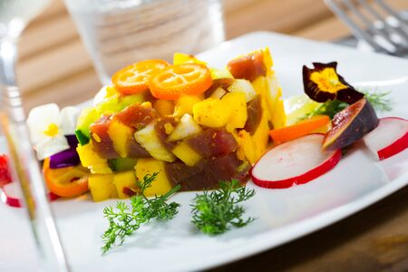 Colorful fish tartare with raw tuna, chopped mango and avocado garnished with cumquat, figs, radish, dill and flowers