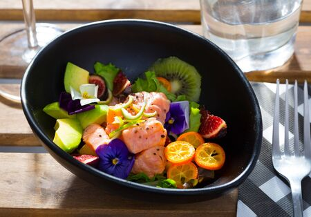 Salmon ceviche with avocado, kiwi and figs served on plate