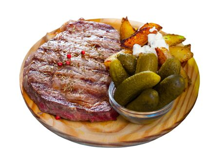 Spicy medium rare roasted veal steak with fried potato wedges with sauce and pickles on wooden board. Isolated over white background