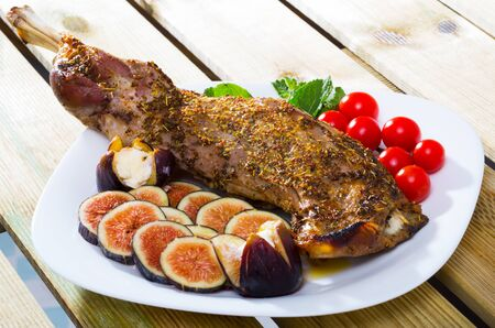 Baked shoulder of mutton in marinade of honey with herbs and mustard grains served with ripe figs, tomatoes, soft cheese and greens