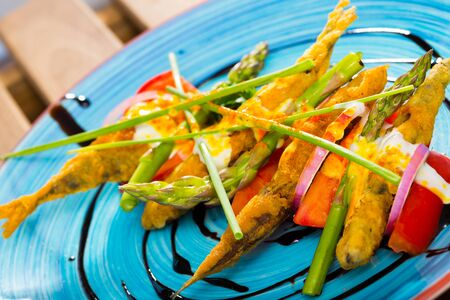 Fried battered anchovies with vegetables and creamy ginger sauce, served on blue plate Stok Fotoğraf - 129918194