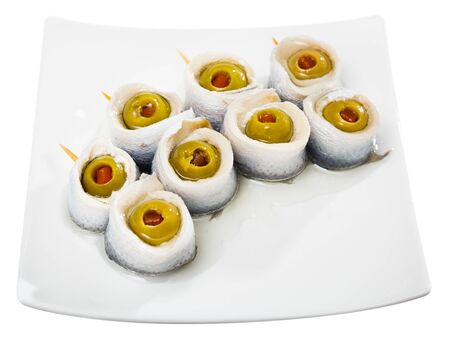 Appetizing pickled herring rolls with stuffed olives served on white plate. Isolated over white background