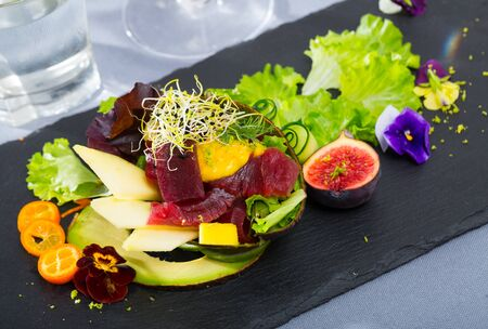 Salad of raw tuna with mango and avocado garnished with figs, kumquat, greens and heartsease flowers