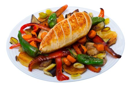 Bulgarian cuisine. Baked vegetables with spicy braised chicken breast (Plakia) on white plate. Isolated over white background