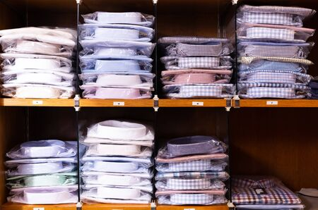 Large assortment of shirts displayed on shelves in men clothes shop Banque d'images - 129857530