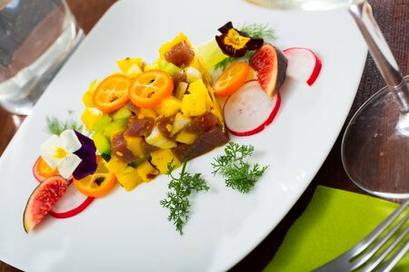 Plate of delicious tuna tartar with mango, avocado, figs and kumquat served on plate Stock Photo
