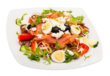 Shepherd salad – traditional Bulgarian dish. Consist of cucumbers, tomatoes, brynza (salted goat cheese) and prosciutto. Isolated over white background