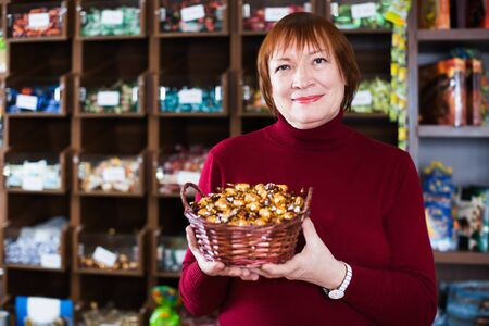 Aged woman holding basket with candies and choosing in the supermarket Foto de archivo - 129908927