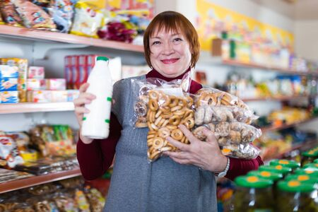 Smiling woman buyer choosing bakery products and drink in the food store Foto de archivo - 129908933