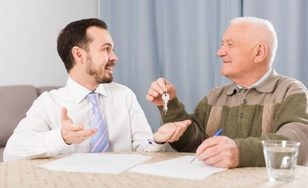 Elderly man and young agent sign contract of rent apartments and hand over keys