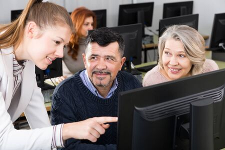 Computer lessons for adults. Young female tutor explaining to mature people how to use computers in classroom