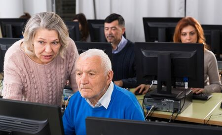 Friendly mature woman helping senior man to use computer during computer classes at university of third age
