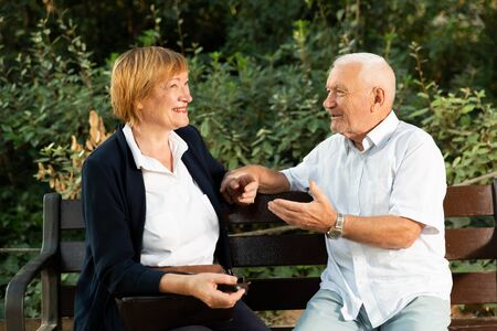 Happy senior man and woman having conversation on bench in green park 写真素材