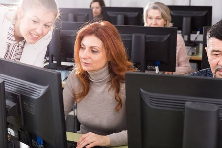 Portrait of mature woman attentively listening young female coach during computer classes at university of third age