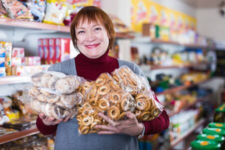 Portrait of positive mature woman holding bakery products in the food store Foto de archivo - 129909052