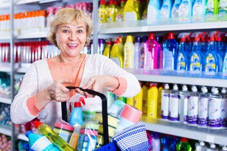 Consumidor de mujer positiva alegre feliz con productos químicos domésticos en la canasta para limpieza Foto de archivo