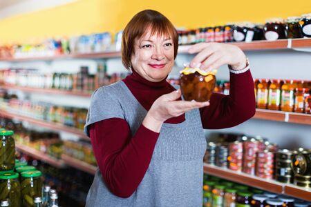 Mature happy smiling female in the shop holding preserved jar of jam Foto de archivo - 129909308