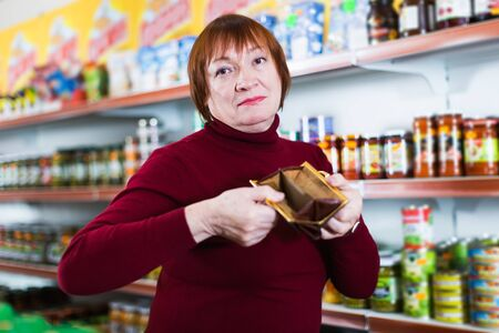 mature unhappy woman customer with wallet without money in food store Foto de archivo - 129909355