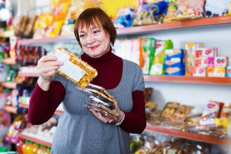mature female buyer choosing honey and nut bar in the food shop