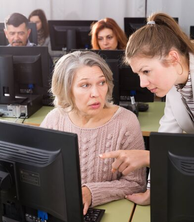 Young female teacher explaining computer skills to mature woman in university class Stockfoto