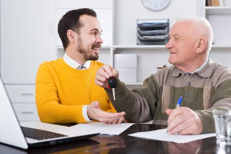 Old man and manager signed car purchase contract at office and hand over keys