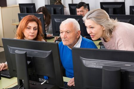 Three coworkers  working around computer monitor, talking about new project in modern office