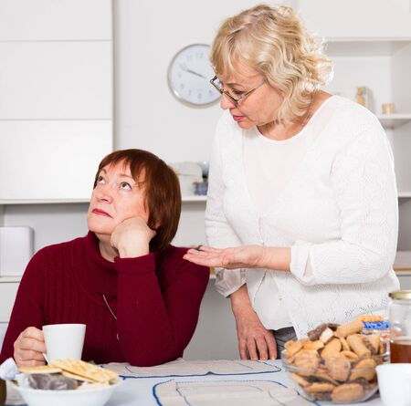 Pensioners females quarreling at kitchen near food at the table