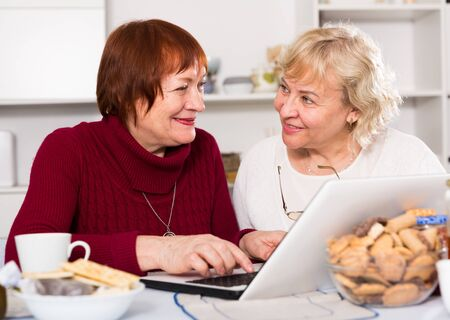 Smiling pensioners females talking at kitchen with laptop at home