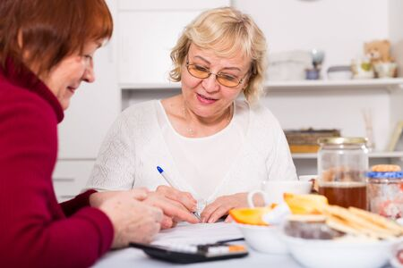 Cheerful elderly women sitting at kitchen table working with documents