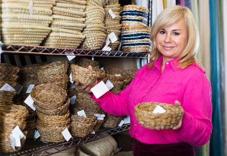 Adult customer standing with wicker basket in store for decor Foto de archivo - 129914045